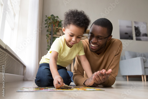 African father and little son collect jigsaw puzzle at home Fototapet