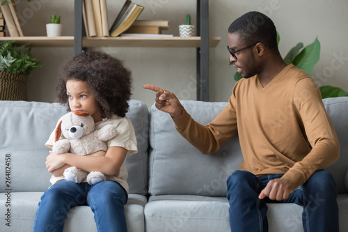 Cuadros en Lienzo African dad scolding for discipline stubborn daughter sitting on sofa