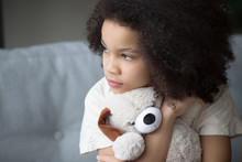 Unfortunate Stray Biracial Kid Girl Embrace Stuffed Toy Looking Aside