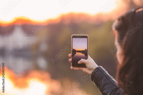 Foto  woman taking picture of sunset on her phone