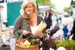 Sympathische Frau auf dem Markt kauft Spargel