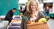Frau mit einem vollen Obst- und Gemüsekorb auf dem Markt