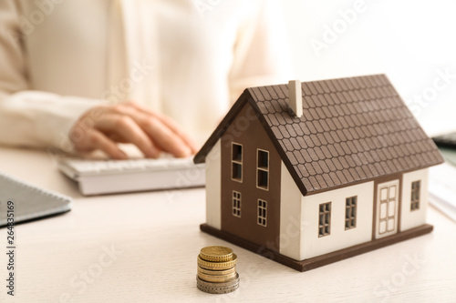 Fotografía  Model of house and money on table of real estate agent