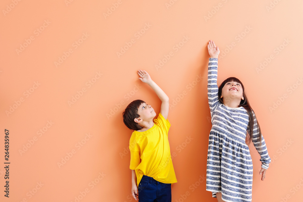 Fototapety, obrazy: Cute little children measuring height near color wall