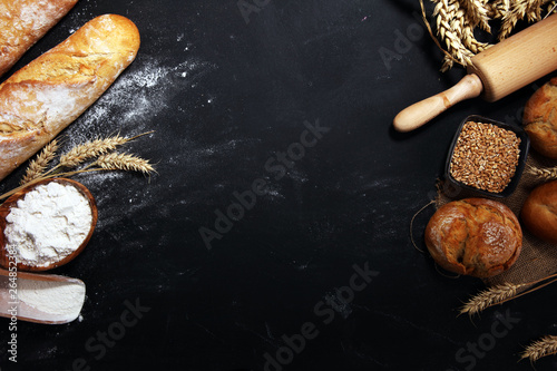 Photo sur Aluminium Boulangerie Assortment of baked bread and bread rolls on rustic black bakery table background