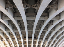 Perspective View Of Curved Arch Shaped Steel Girders Under An Old Road Bridge With Rivets And Struts Painted Grey