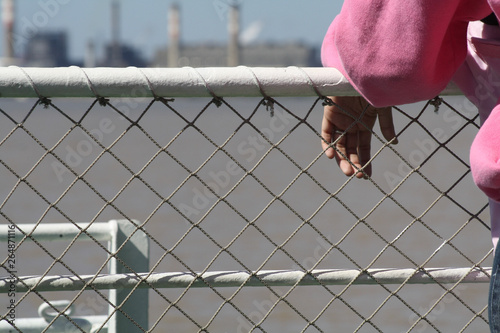 Photo Mano reposada sobre un alambrado con industrias de fondo