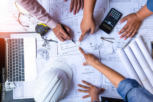 Obraz engineers pointing to building on blueprint and using laptop to drawing design building Project in office, construction concept. Engineer concept - fototapety do salonu