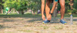 Young athlete man tying running shoes in the park outdoor, male runner ready for jogging on the road outside, asian Fitness walking and exercise on forest trail in morning. wellness and sport concepts