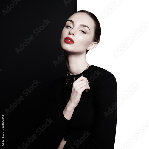 La pose en embrasure womenART beautiful young woman with black bijouterie pose in studio