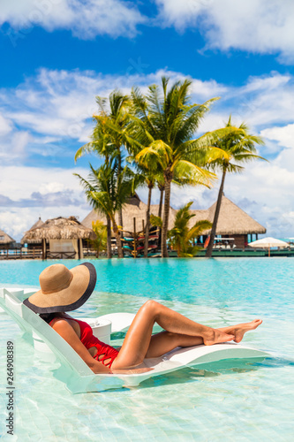 Fotografia Luxury hotel swimming pool woman relaxing in lounging chair enjoying summer vacation