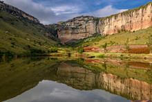 Sandstone Cliffs Reflecting In A Dam In The Golden Gate National Park In South Africa Freestate.