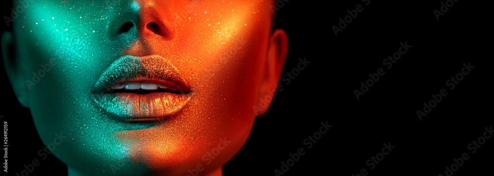 Fototapeta Fashion model woman face in bright sparkles, colorful neon lights, beautiful sexy girl lips. Trendy glowing gold skin make-up. Glitter metallic shine makeup