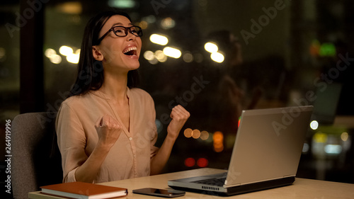 Fotografering  Excited female showing yes gesture sitting laptop, celebrating work success