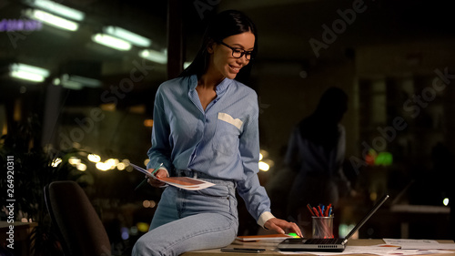 Smiling female architecture browsing website on laptop, creative profession
