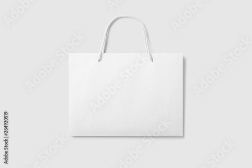 Photo Mockup of a blank white paper shopping bag with handles on light grey background