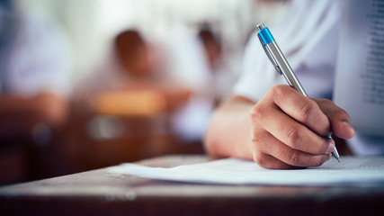 Hand of students taking exam with stress in classroom