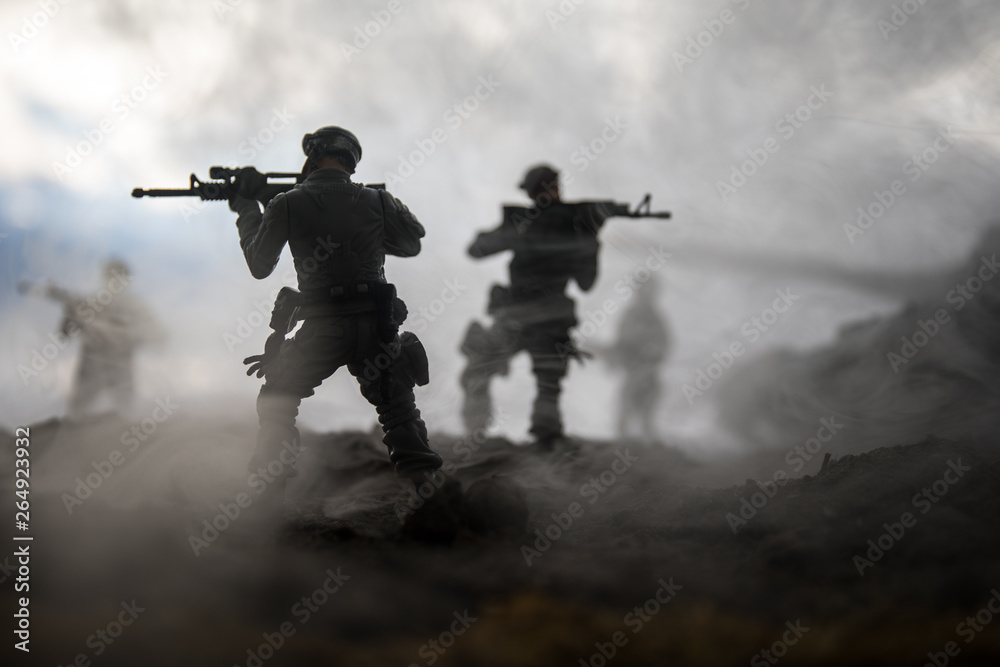 Fototapeta War Concept. Military silhouettes fighting scene on war fog sky background, World War Soldiers Silhouettes Below Cloudy Skyline at sunset. Attack scene. Armored vehicles.