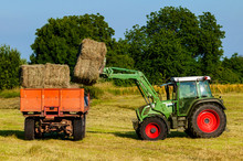 Green Tractor Loading Hay Bale...