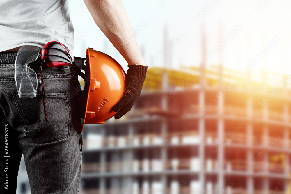 Fototapety, obrazy: A builder, an architect holds in his hand a construction helmet against the background of a construction site, a tape measure. Concept architecture, construction, engineering, design, repair.
