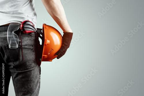 Fotografía  The builder, the architect holds in his hand a construction helmet on a light background, a tape measure