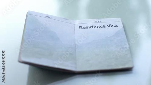Slika na platnu Residence visa, opened passport lying on table in customs office, travelling