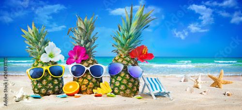Fotografía  Attractive pineapples in stylish sunglasses on the sand beach against turquoise