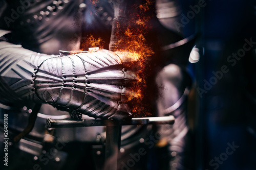 Photo Close up of a Medieval steel armour with iron glove hand bursting with flames of