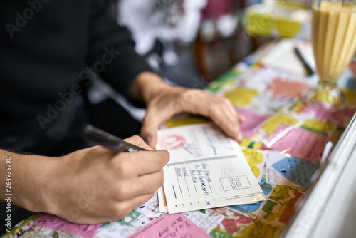 Fototapeta Person writes message on postcard in unusual cafe obraz