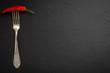 Papryczka chili nadziana na starym ozdobnym widelcu na czarnym tle kamienia łupkowego