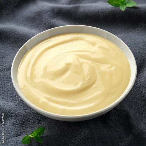 Photo Bowl of vanilla custard on rustic background
