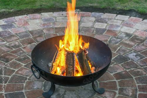 Photo Geschmiedeter Feuerkorb mit wärmenden Feuer auf schönem Pflastersteinkreis im Ga