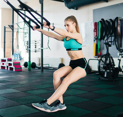 Fototapeta Fitness / Siłownia Fit woman exercising with fitness straps in the gym. Functional training. Sports lifestyle.