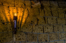 Lighted Medieval Castle Torch Hanging On A Stone Wall, Vintage Objects And Background