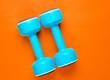 Leinwanddruck Bild - Two blue plastic dumbbells on orange background Sport, fitness concept. Top view. Minimalism