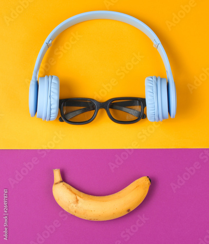 Magasin de musique Minimalism flat lay concept. Smiling face listens to music. Headphones, 3D glasses, banana on purple yellow background. Top view