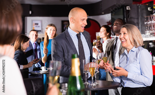 Fotografia  Cheerful middle aged woman with male colleague enjoying office party in bar, tal