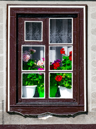 Photo A wooden window outside the house with flowering geranium flowers in an old traditional European house