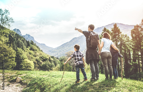 family on a green meadow looking at the mountain panorama