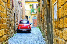 View Of A Small Red Car In The Historic Cityscape In Orvieto, Italy.