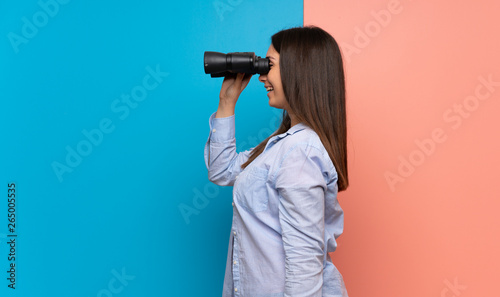 Fotografie, Obraz  Young woman over pink and blue wall and looking in the distance with binoculars