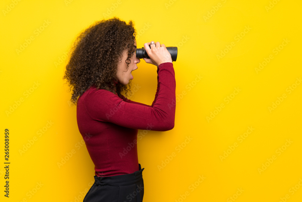 Fototapety, obrazy: Dominican woman with turtleneck sweater and looking in the distance with binoculars