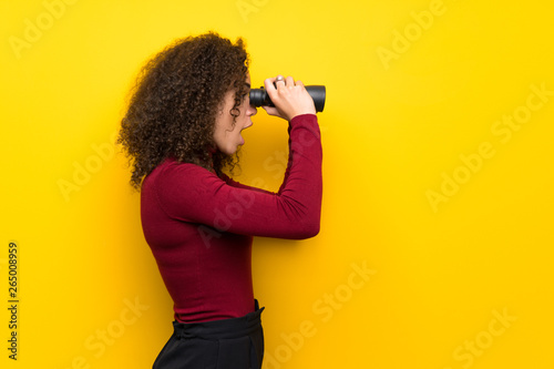 Fotografia  Dominican woman with turtleneck sweater and looking in the distance with binocul