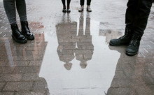 Reflection Of A Group Of People, Four Pairs Of Legs And A Pair Guy And Girl In A Puddle On The Road