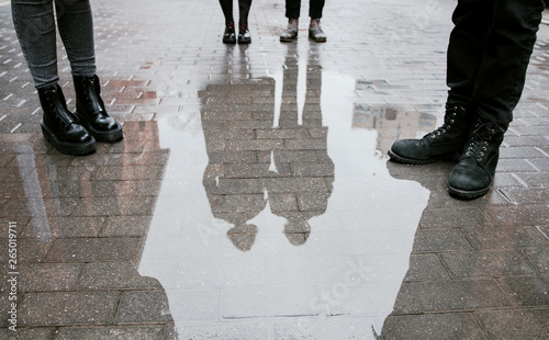 Cuadros en Lienzo Reflection of a group of people, four pairs of legs and a pair guy and girl in a