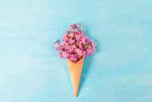 Ice Cream Cone With Spring Blossom Pink Cherry Or Sakura Flowers On Blue Background. Minimal Spring Concept. Flat Lay