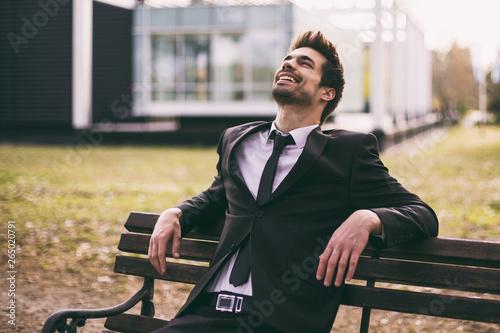 Fotografia  Happy elegant businessman smiling and enjoys sitting outdoor
