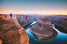 Hiker Overlooking Horseshoe Bend At Sunset, Arizona, USA