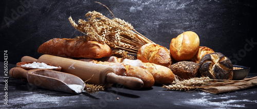 Papiers peints Boulangerie Assortment of baked bread and bread rolls on rustic black bakery table background