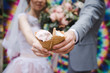 canvas print picture - The bride and groom are eating ice cream together on a bright wall background. Funny newlyweds eat ice-cream. Happy Wedding Day